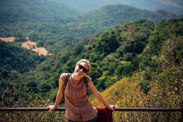 La ragazza sta sul punto di vista e sorride il giorno soleggiato. il turista femminile felice gode di bello panorama.