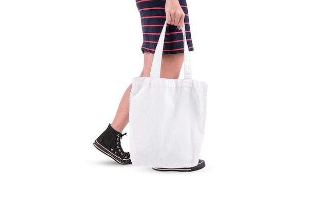 La ragazza sta tenendo il modello in bianco del modello della borsa di totalizzatore isolato su fondo bianco.