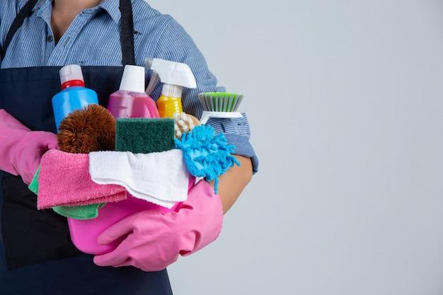 La ragazza sta tenendo il prodotto, i guanti e gli stracci di pulizia nel bacino sulla parete bianca