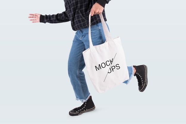 La ragazza sta tenendo il tessuto di tela borsa per modello vuoto mock-up isolato su sfondo grigio.