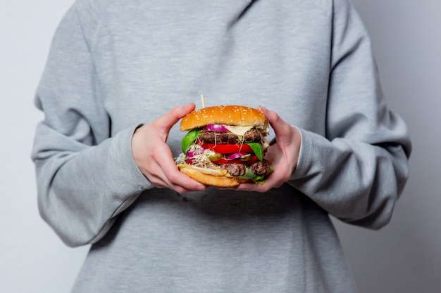 La ragazza sta tenendo in mano un hamburger su spazio bianco