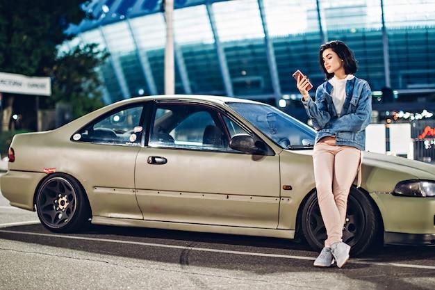 La ragazza sta vicino all'automobile e usa lo smartphone alla sera