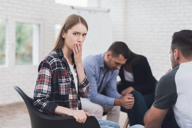 La ragazza stordita è seduta nella sessione di terapia di gruppo.