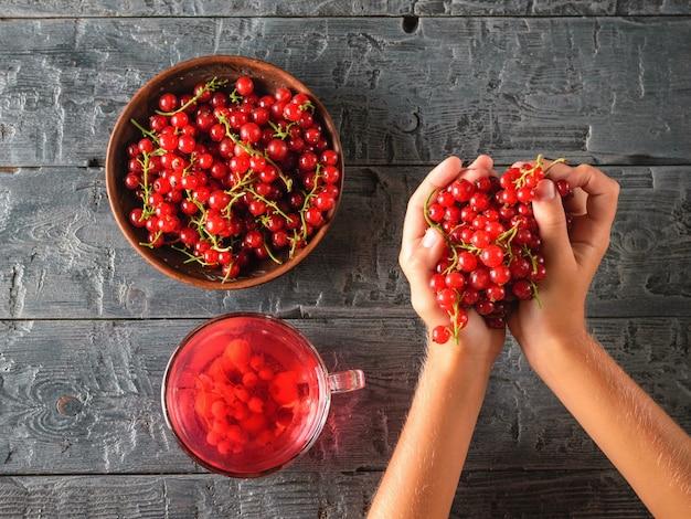La ragazza stringe una manciata di bacche fresche di ribes rosso sul tavolo del villaggio.