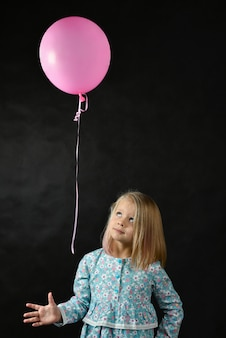 La ragazza su uno sfondo nero soffia un palloncino