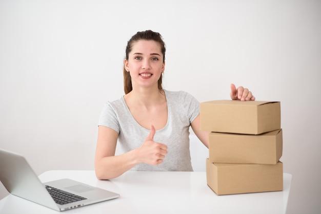 La ragazza su uno spazio luminoso si siede a un tavolo con un computer e scatole di corton e mostra il pollice in su. concetto di servizio di consegna