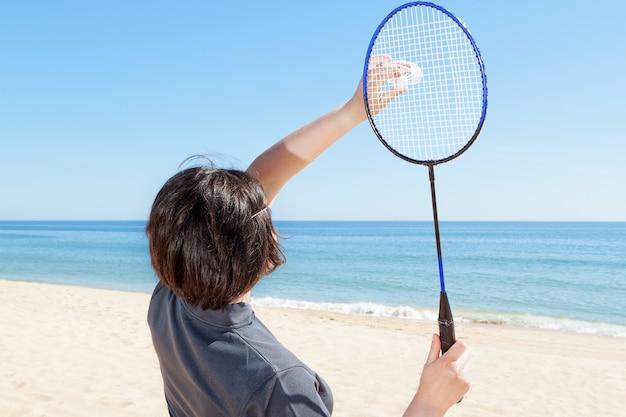 La ragazza sulla spiaggia serve a giocare a badminton. avvicinamento.