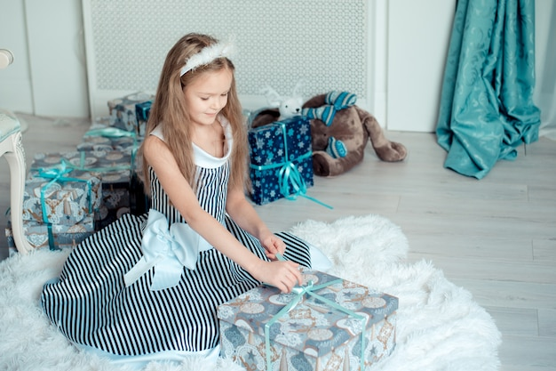 La ragazza sveglia apre i regali nella stanza della decorazione di natale. tonica