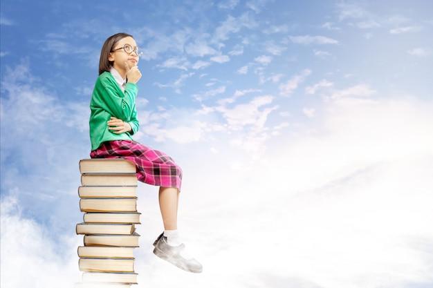 La ragazza sveglia asiatica con i vetri pensa mentre si siede sulla pila di libri con cielo blu