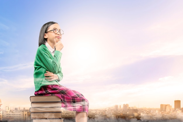 La ragazza sveglia asiatica con i vetri pensa mentre si siede sulla pila di libri con la città e il cielo blu