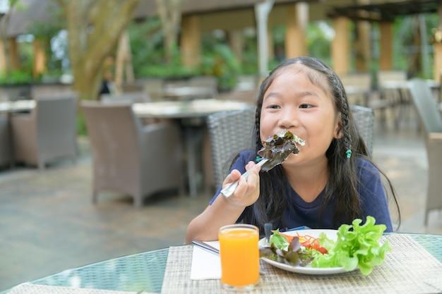 La ragazza sveglia asiatica gode di di mangiare l'insalata vegetariana