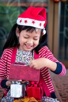 La ragazza sveglia asiatica riceve i regali di festa con l'eccitazione