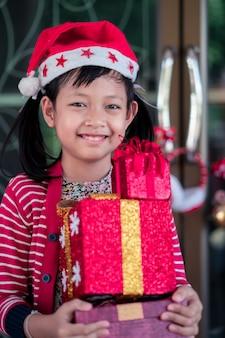 La ragazza sveglia asiatica riceve il regalo di festa con l'eccitazione