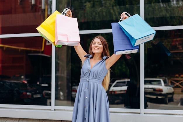 La ragazza sveglia con i sacchetti della spesa colorati cammina intorno al centro commerciale