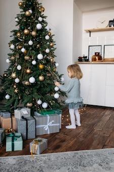 La ragazza sveglia del piccolo bambino sta decorando l'albero di natale all'interno