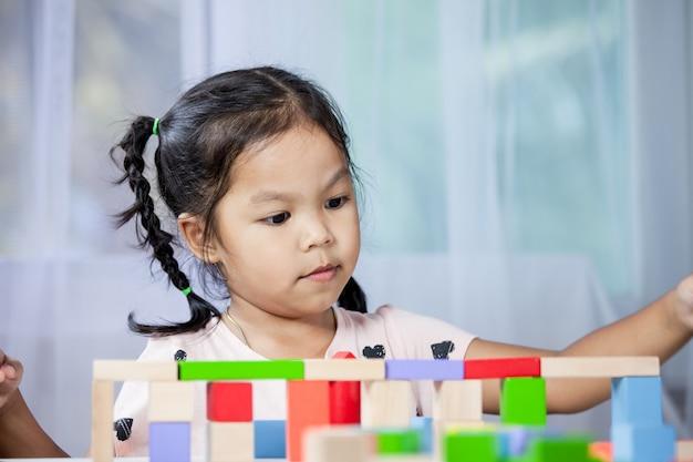 La ragazza sveglia del piccolo bambino sta giocando con i blocchi di legno variopinti nella stanza