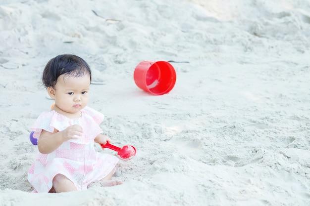 La ragazza sveglia del primo piano fa un fronte deformato quando la sabbia entra nella sua bocca sulla priorità bassa strutturata della spiaggia