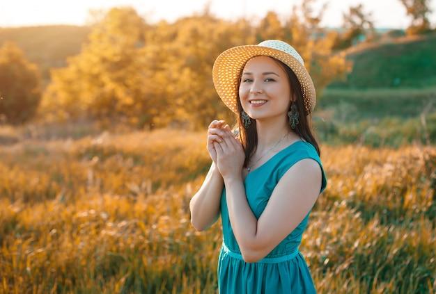 La ragazza sveglia della giovane donna gode del tramonto caldo dell'estate