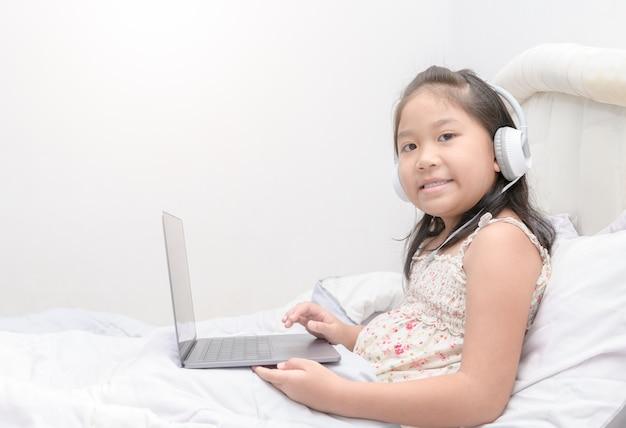 La ragazza sveglia gioca il computer portatile e musica d'ascolto
