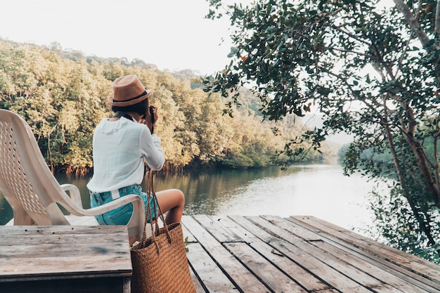 La ragazza sveglia gode di con la natura che riposa e che osserva sul fiume.
