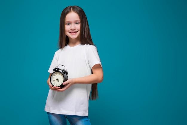 La ragazza sveglia in maglietta con capelli lunghi tiene l'orologio