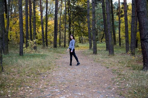 La ragazza sveglia in un maglione grigio è mezzo giro sulla strada nella foresta di autunno.