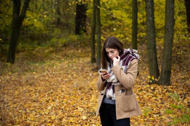 La ragazza sveglia in una giacca marrone e una grande sciarpa sta meditatamente e guarda nel telefono nella foresta di autunno.