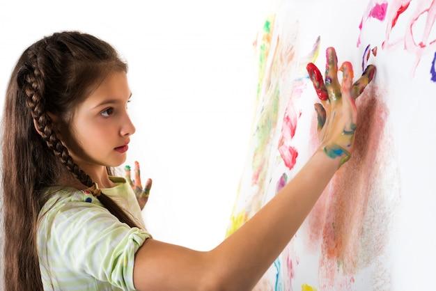 La ragazza sveglia mostra le mani macchiate pittura su bianco