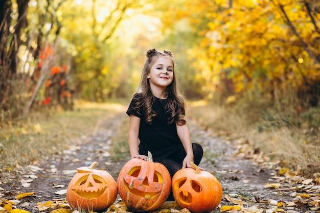 La ragazza sveglia si è vestita in costume di halloween all'aperto con le zucche
