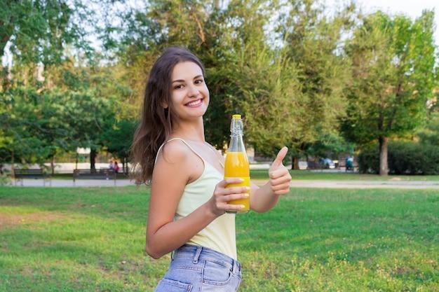 La ragazza sveglia sta facendo una passeggiata nel parco che tiene una bottiglia di succo d'arancia in un giorno soleggiato di wam