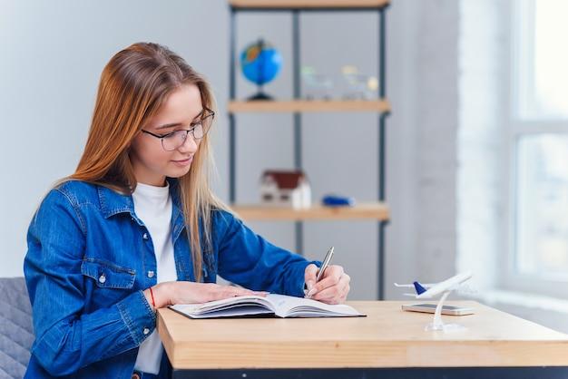 La ragazza teenager allegra ai vestiti del denim studia a casa.
