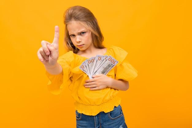 La ragazza teenager bionda mostra i soldi su una priorità bassa gialla con la copia