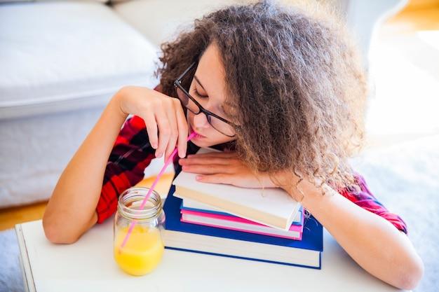 La ragazza teenager dei capelli ricci beve il succo e riposa sui libri