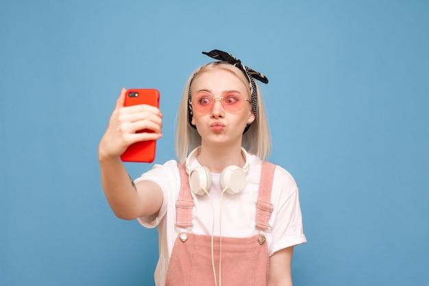 La ragazza teenager divertente fa il selfie su uno smartphone, indossando abiti luminosi e occhiali da sole rosa
