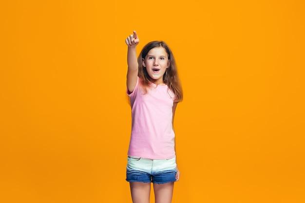 La ragazza teenager felice che indica a voi, ritratto del primo piano di mezza lunghezza su priorità bassa arancione.