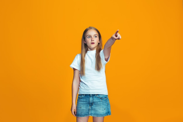 La ragazza teenager felice che indica te, ritratto del primo piano di mezza lunghezza su spazio arancio.