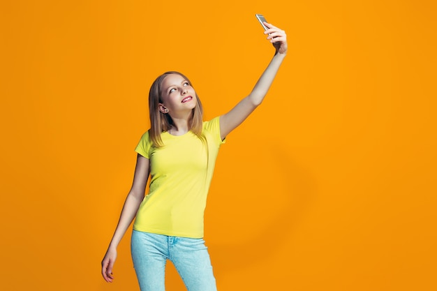 La ragazza teenager felice che sta e che sorride contro la parete arancio