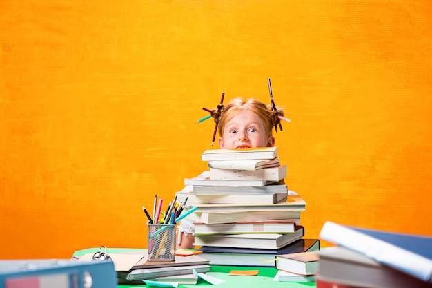 La ragazza teenager rossa con molti libri a casa.