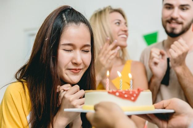 La ragazza teenager sveglia della festa di compleanno ha pregato per la benedizione prima di soffiare la torta di compleanno.