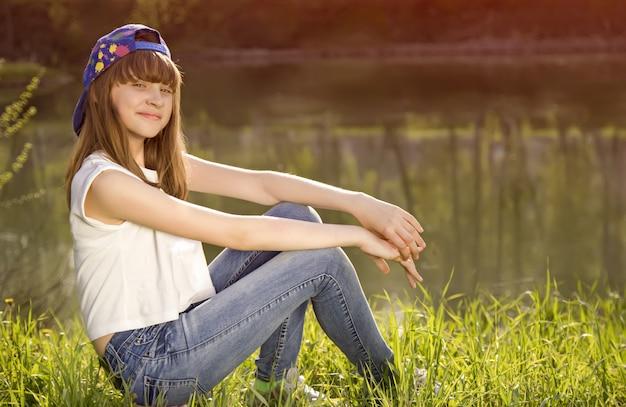 La ragazza teenager sveglia si siede su un'erba vicino al lago
