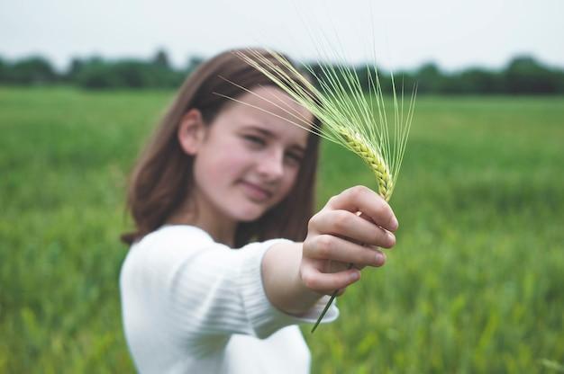 La ragazza teenager tocca le mani con le piante verdi nel giardino