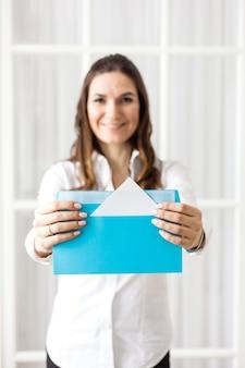 La ragazza tiene busta, busta con lettera o commissione, compito
