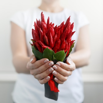La ragazza tiene con entrambe le mani un piccolo bouquet fatto di peperoncino rosso a forma di cuore