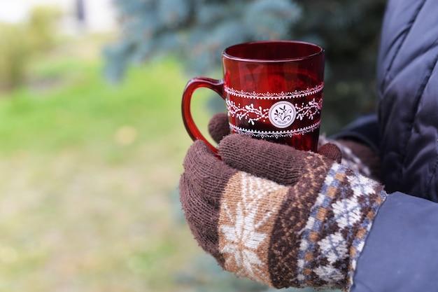 La ragazza tiene i guanti a maglia in guanti askus con un caffè bevanda di riscaldamento
