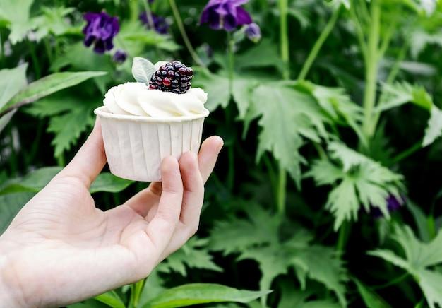La ragazza tiene in mano cupcakes con panna montata e blackberry.