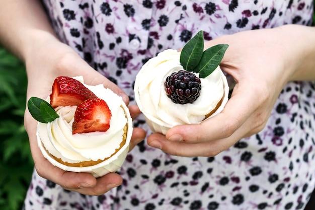 La ragazza tiene in mano cupcakes con panna montata e fragole e mora.