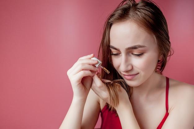 La ragazza tiene in mano le punte dei capelli e la mano destra le applica olio giallo.