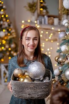 La ragazza tiene in mano un cesto di giocattoli di natale. il cesto metallico in pieno della decorazione d'annata dorata dell'albero del nuovo anno o di natale gioca in mani della ragazza, fuoco selettivo.