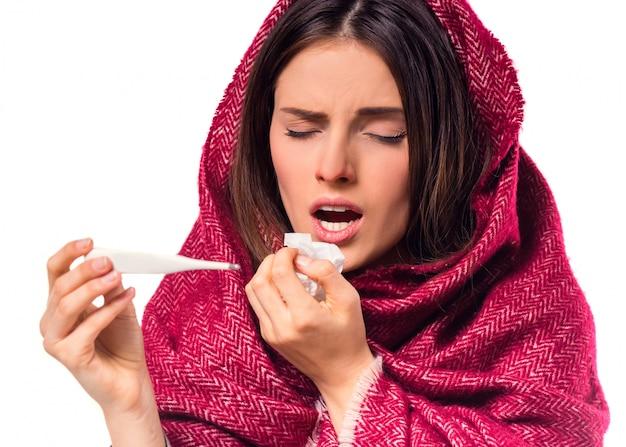 La ragazza tiene in mano un termometro e starnutisce.