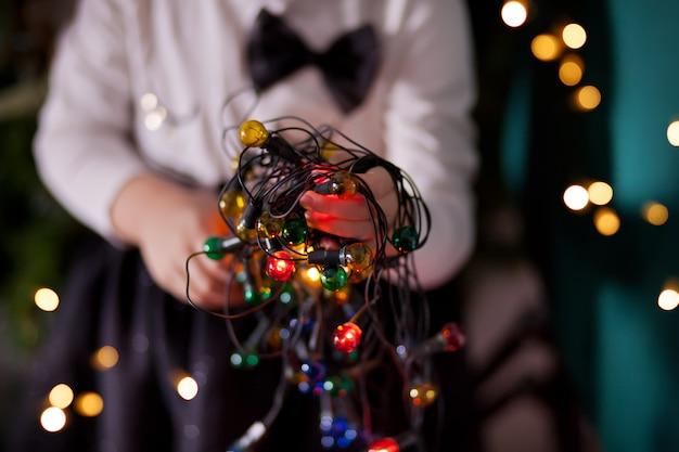La ragazza tiene in mano una ghirlanda natalizia.